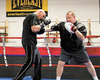 Kelly Pavlik spars with trainer Jack Loew at the South Side Boxing gym in preparation for his title defense.