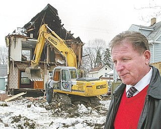 Struthers Mayor Terry Stocker watches as employees of Maverick Contractors of Lisbon demolish a house at 203 Poland Ave. in Struthers Wednesday.