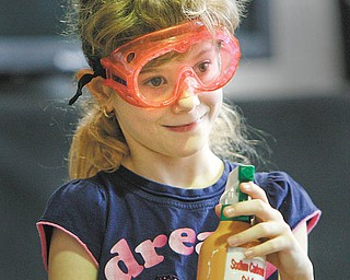 """Lloyd Elementary second-grader Mercedes Willis gets ready to spray a chemical agent to find another clue in the search for the missing slime ingredients during a """"Simply Chemistry"""" assembly with COSI."""