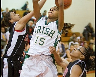 Geoffrey Hauschild The Vindicator.Ursuline's Dominique Jenkins (15) meets resistence on her way to the hoop from Campbell's Tashira Uceta (1) and Jayaira Grhim (15) during the third quarter at Mineral Ridge High School on Saturday afternoon.