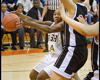 Geoffrey Hauschild The Vindicator.Ursuline's Briana Curd (24) keeps the ball at a safe distance from Campbell's Tiffany Colon (25) while driving to the basket during the third quarter at Mineral Ridge High School on Saturday afternoon.