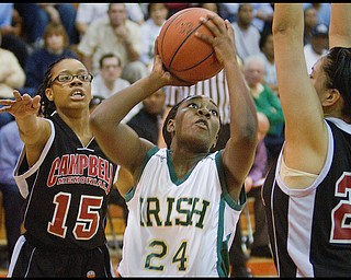 Geoffrey Hauschild The Vindicator.Ursuline's Briana Curd (24) takes aim while defended by Campbell's Jayaira Grhim (15) and Tiffany Colon (25) during the third quarter at Mineral Ridge High School on Saturday afternoon.