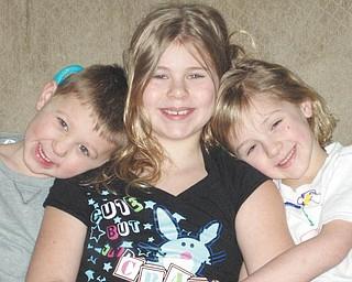 Morgan, 11, Hannah, 8, and Robby, 6, Kist at home last May..