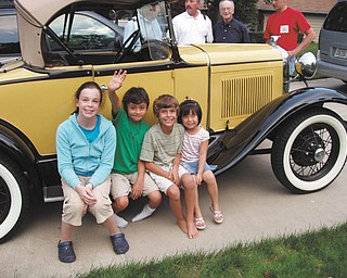 This is a photo of a 1930 Ford Model ÒAÓ taken by owner R.J.Wittenauer of Boardman.The children were taken for a ride on this day and are as follows, from left: Lauren McIntosh of Poland, Christian and Connor McIntosh, both of North Jackson, and Jillian McIntosh of Poland. In the background are, from left, Dr. Robert McIntosh, father of Christian and Connor; William McIntosh, the childrenÕs grandfather; and James McIntosh, father of Lauren and Jillian..