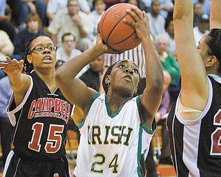 Geoffrey Hauschild|The Vindicator.Ursuline's Briana Curd (24) takes aim while defended by Campbell's Jayaira Grhim (15) and Tiffany Colon (25) during the third quarter at Mineral Ridge High School on Saturday afternoon.