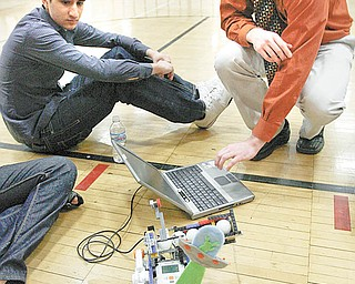 Faisal Mangalji, left, and Shaun Hardin, both seniors and members of the Howland High School robotics team, use a computer to adjust their robot, Jeffrey, for the 12th Northeast Ohio Robotics Education Program competition. The team and Jeffrey took the overall top prize in the high school division at Wednesday's event at Youngstown State University.