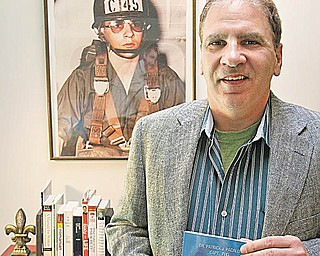 """Patrick Pacalo stands in his Boardman home holding a copy of his latest book, """"Eastern Europe: Cold Warfare III."""" The photo on the wall is of Pacalo at age 17 in the Pa. Army National Guard."""