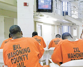 Inmates sit in a television-viewing pod at the Mahoning County jail in downtown Youngstown. County officials will be in federal court in Cleveland on Wednesday, seeking permission to close half the jail and lay off one-third of the sheriff's staff, effective March 28.