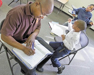 Wasilwa Mwonyonyi, left, of Eta Zeta chapter of Iota Phi Theta fraternity, tutors Christian Armour, a 5-year-old who attends Youngstown Christian School, and Matthew Walton, 13, a student at Volney Rogers Middle School, in math and history. The tutoring session occurred at the Buckeye Neighborhood Youth Center on the city's North Side.