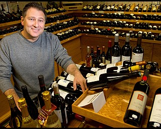 The Vindicator/Geoffrey Hauschild.President of Vintage Estate, Phil Reda, poses for a portait with some of the more than 1,000 types of wine at Vintage Estate along South Ave. on Tuesday afternoon.