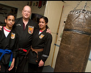 The Vindicator/Geoffrey Hauschild.Ben Powell, 13, ?Todd? Vea, and Heather Powell, 17, pose for a portrait during a lesson at AE Vea Karate along Belmont on Friday afternoon.