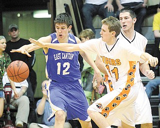 C.J. Peaco, right, of Newton Falls and Stuart Campbell of East Canton go after a loose ball during the Division III regional semifinal basketball game at the Canton Fieldhouse on Wednesday night. Newton Falls advanced with a 60-48 win.