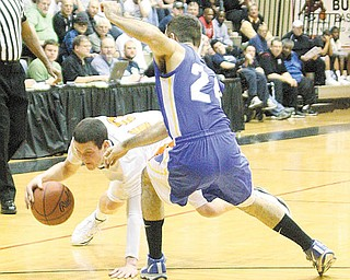 BBALL - Cody Dillion looses his balance as (24) Jon Cartwright plays defense Wednesday night in Canton. - Special to The Vindicator/Nick Mays