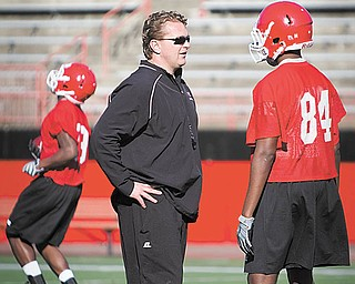 YSU's Head Coach Eric Wolford talks with Jelani Berassa (84) during drills at YSU's spring football practice in Stambaugh Stadium on Wednesday afternoon.