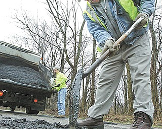 Tim Heitzenrater, left, an equipment operator, and Frank Kordupel, a foreman, both of Teamsters Local 377 and employees of the Mahoning County Engineer's Office, patch potholes on New Castle Road in Poland Township on Tuesday.