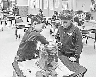 The Vindicator: Pupils in Elaine Scott's first-grade class at St. Patrick School in Hubbard have been looking forward to spring as they studied about the environment and have become interested in Earth Day. Among the youngsters who are planting seeds to surprise their moms with gifts of gold (marigolds) this spring are, from left,  Michael Anderson and Jeffery Hazy.