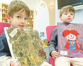 Brothers Kosta, 3, left, and Andrew, 4, Cvercko show off artwork they made at the Goddard School in Boardman.