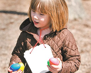 Emma Haase runs through the playground with her holiday bounty during the Easter egg hunt Tuesday sponsored by the Boardman Kiwanis for kindergarten students at Boardman schools.