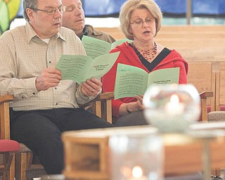 Tom and Karen Lazor of Howland sing one of the songs, a repetitious style of music called ostinato, during Taizé prayer.