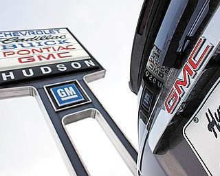 In this Feb. 7, 2010 photo, a 2010 GMC Acadia sits under the sign at a General Motors dealership in Silverthorne, Colo. General Motors Co. said Thursday, April 1, 2010, its March sales rose 21 percent over the same month last year, a sign that an incentive war will boost overall U.S. auto sales.