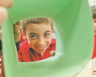 Petros Atsas peers through a folded piece of paper that was to become an Easter basket.