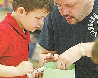 Collin Michaels gets some help from his dad, Rick Michaels, during the Easter project.