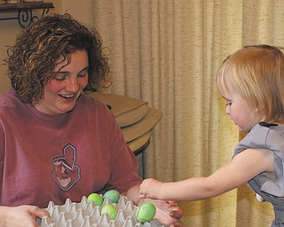 While visiting her grandparents, Mike and Laurie Fox of Lowellville, 2-year-old Ashlynn Mason enjoyed coloring eggs and sharing them with her mom, Beth..