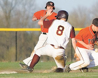 eld's Cody Pitzo watches as South Range's Andy Lacefi eld (8) arrives safely at second as the Tigers' Ronnie Bovo (11) bobbles the ball during the sixth inning of Tuesday's game at the new South Range High School in North Lima. The Raiders defeated the Tigers 13-6.