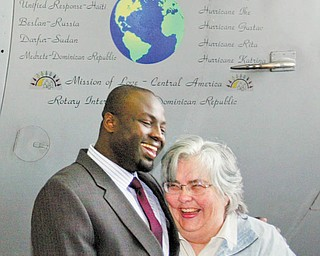 Dr. Michael K. Obeng, chief of plastic surgery at St. Elizabeth Boardman Health Center, and Kathleen M. Price, founder and director of Mission of Love, stand beneath the nose art on a C-130 Hercules cargo plane unveiled Wednesday . The 910th has transported 380,000 pounds of humanitarian aid for the Mission of Love over the last 11 years. R.E.S.T.O.R.E. Worldwide Inc., founded by Dr. Obeng, is planning a humanitarian mission to Ghana in the near future.