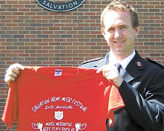 The Vindicator: Captain John Brand of the Salvation Army in Salem  on  .Monday displays a shirt being sold to help raise funds for the needy  .next Christmas while standing by the army's large kettle..