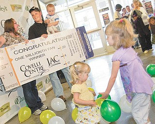 Alexis and Madison Beaudis, ages 2 and 4, play among balloons that fell from the ceiling as Jessica and Adam Hayes along with their 1-year-old son Caiden were recognized at the Covelli Centre as the 1 millionth patron Tuesday evening.