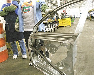 Irene Torres of Austintown, left, and Bertha Brown of Warren, launch-team trainers for the Chevrolet Cruze, show off the side intrusion bar inside the door of the Cruze. The bar, made of high-strength steel, helps prevent the door from collapsing in the event of a crash.