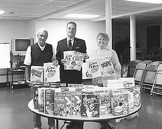 "Serial cereal packers: Austintown Kiwanis members Dave Ritchie, left, Keith Leonard (president) and Joyce Pogany (Lt. Governor) recently packed cereal for donation to the Salvation Army. ""Kiwanis Cereal Day"" takes place each month at the Austintown club, and members have collected more than 250 boxes of cereal to be donated to needy families. This fulfills the Kiwanis' goal of making young children Priority One."
