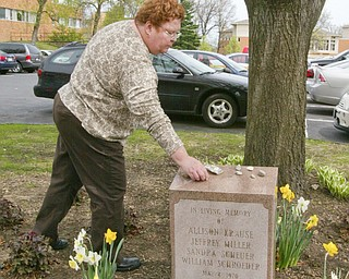 Jane Doughton, a Valley resident who was a student at Kent State on May 4, 1970 when 4 students were killed by Ohio National Guard gunfire, places a stone on a memorial to the 4 students.