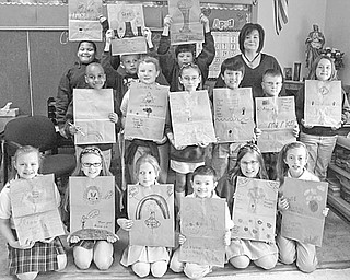 Students in Mrs. Kelly Kryonich's third-grade class at St. Patrick School in Hubbard display the brown-paper grocery bags they decorated with messages and pictures to remind people to protect the earth. Bags for the Earth Day project were donated by Devine's Shop and Save in Hubbard and will be returned to the store and passed on to customers with their grocery purchases.