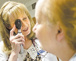 "Deborah Hromyak, a certified nurse practitioner, conducts an eye examination on one of her patients, Susan Walters of Austintown. Walters, who has had cancer and heart-valve damage among other medical problems, says she doesn't think of Hromyak as ""not being a doctor. For general medical information, I think she knows as much or more than any doctor I've been to."""