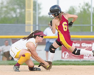 Mooney's Margo Ucchino makes it past Walsh's Calia Battista (4) untagged as Battista fi elds a ground ball during the fifth inning of Wednesday's game at Boardman's Fields of Dreams.
