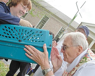 Hidden by the carrier, Phoebe, a longhaired tuxedo cat, receives a blessing. Holding the carrier is Phoebe's owner, Barbara Jones of Austintown.