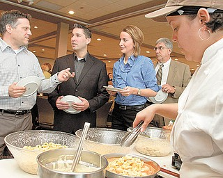 Liz Irizarry of Youngstown, right, prepares cheese tortellini as, from left, Todd Marian of Help Hotline, Scott Landy of First National Bank, Lauren Lindvig of WFMJ and Alfred J. Pasini, executive director of Youngstown Hearing and Speech Center, wait in the food line during the annual meeting of the Community Corporation, parent organization of United Way of Youngstown and the Mahoning Valley at The Lake Club, Poland.