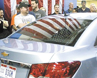 A group of GM Lordstown employees gathers around a Chevrolet Cruze after a benefit motorcycle ride through the plant. Production of the Cruze is expected to begin at the plant in July.