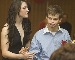 LISA-ANN ISHIHARA   THE VINDICATOR...Lindsay Lewis, 17, helps her brother Nick Lewis, 16, Canfield., at the annual tri county special needs prom, held at Anthone's.