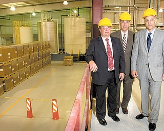 Simon Roofing owners, from left, Anthony Vross, Alex Simon and Jamie Simon, show off their new manufacturing facility in Struthers. The new plant has the potential to employ up to 80 workers.