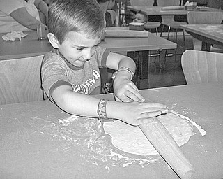Tom and Jill Zidian invited students from Holy Family Preschool and their teacher, Johnna Lewis, to a Mother's Day event at their new Culinary Arts Center, 492 McClurg Road, Boardman, where the youngsters had an opportunity to become chefs for the day. Among those who joined their mothers in making pizza from scratch was Andrew Kali, 4, above, who found rolling pizza dough was a fine art.