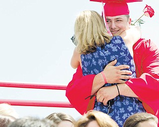Columbiana High School graduate Michael McMaster gets a big hug from his mother, Carrie McMaster, after he presented her with a flower during commencement exercises Sunday in Harvey S. Firestone Park. High school graduations move into full swing over the next two weeks.