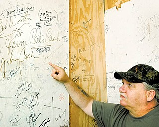 Kerry Smocira, former entertainment director at Ponderosa Park in Salem, points out the signatures of June Carter Cash and Johnny Cash on a backstage wall at the park. The park is closing, and efforts are being made to preserve the wooden panels.