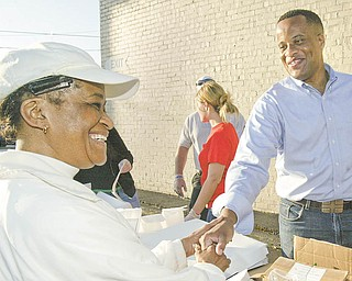 The Vindicator Mayor Jay Williams greets Lillie Caffey of Youngstown during a Monday morning event to observe the 99 th anniv of St. PAtrick church. The church gave away free donuts and coffee Monday morning along Market St in Youngstown.
