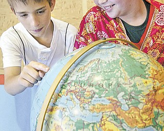 """Ryan Kost and Emily King look a globe during a """"Country Extravaganza"""" on Tuesday at South Side Middle School."""