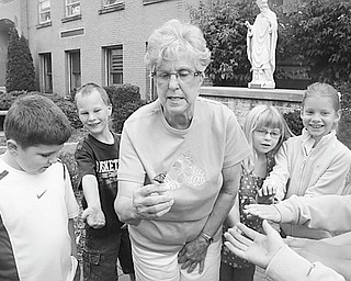 Elaine Scott, above, and members of her first-grade class at St. Patrick School in Hubbard release one of the butterflies they took care of as part of a class project. The students watch the butterflies develop and emerge from cocoons. The class then feeds and takes care of the butterflies until it's time to release them. The project has become a tradition for first-graders.