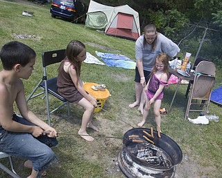 LISA-ANN ISHIHARA | THE VINDICATOR..L-R Tyler Walker, 9, Elizabeth Morgan, 7, Angela Clemens, and Chloe Morgan, 4, all of Niles, roasts food on the first day of Jonesfest at Nelson Ledges Quarry Park.
