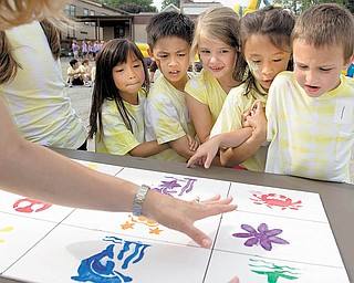 Parent volunteer Lori McGlone explains the memory-board game Wednesday at St. Charles School's end-of-the-school-year picnic in Boardman. First-graders, from left, Ally Schwendeman, Kiet V. Lau, Brie Ruffi ng, Isabella Davis and Tim Falter learned they were supposed to stay attached, by hooking arms or holding hands, and go between two tables to correctly draw the shapes onto paper.